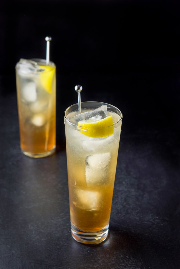 Wider glass in front filled with the Long Island iced tea cocktail