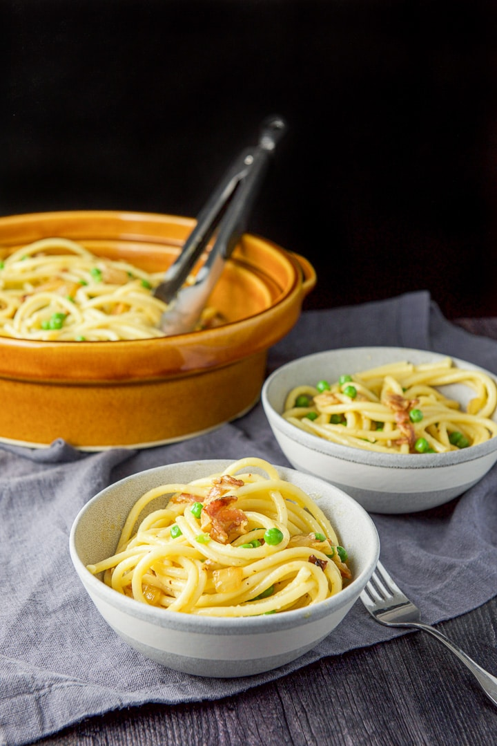 Bucatini carbonara served in two grey bowls
