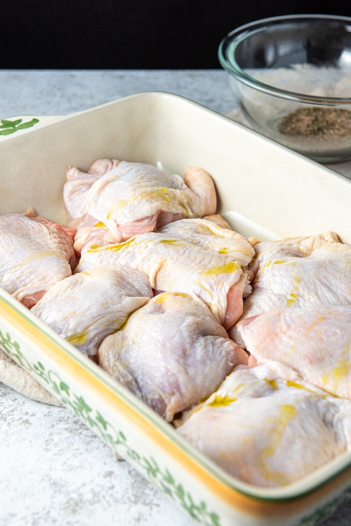 Chicken thighs in a baking dish with olive oil on top for the oven roasted chicken thighs