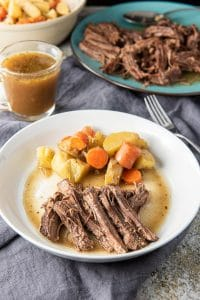 Instant pot bottom round roast on a plate with some veggies