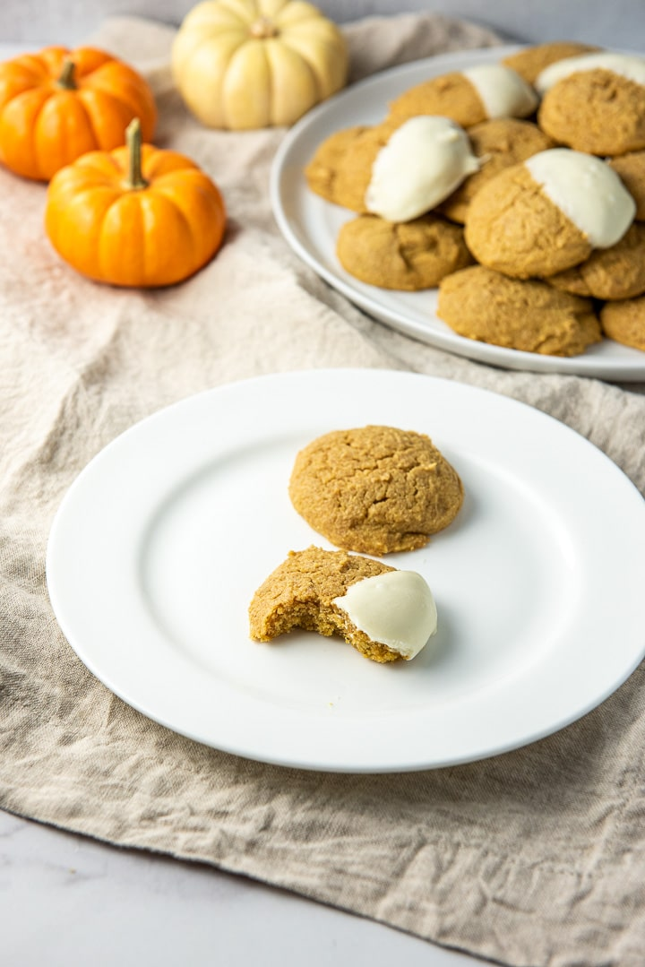 One of the pumpkin cream cheese cookies bitten and on a plate with a whole one