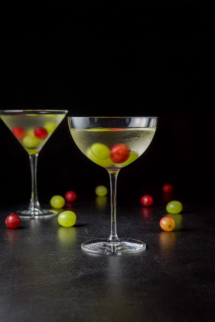 Vertical view of the wide glass filled with the white grape cosmo