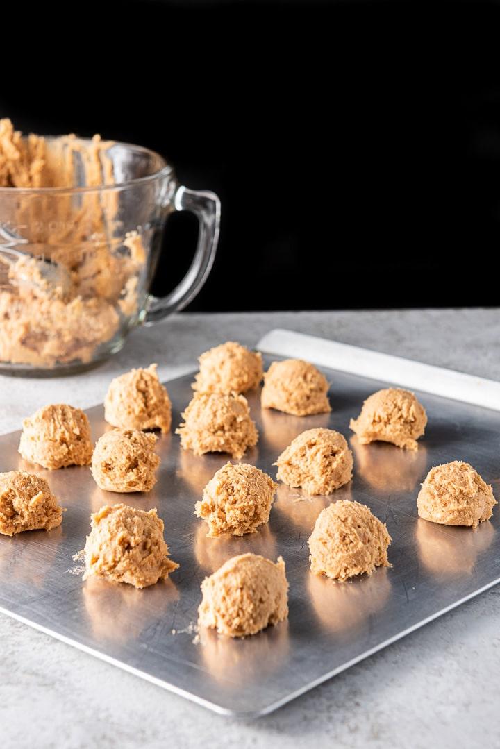 Balls of butterscotch cookies batter on a cookie sheet