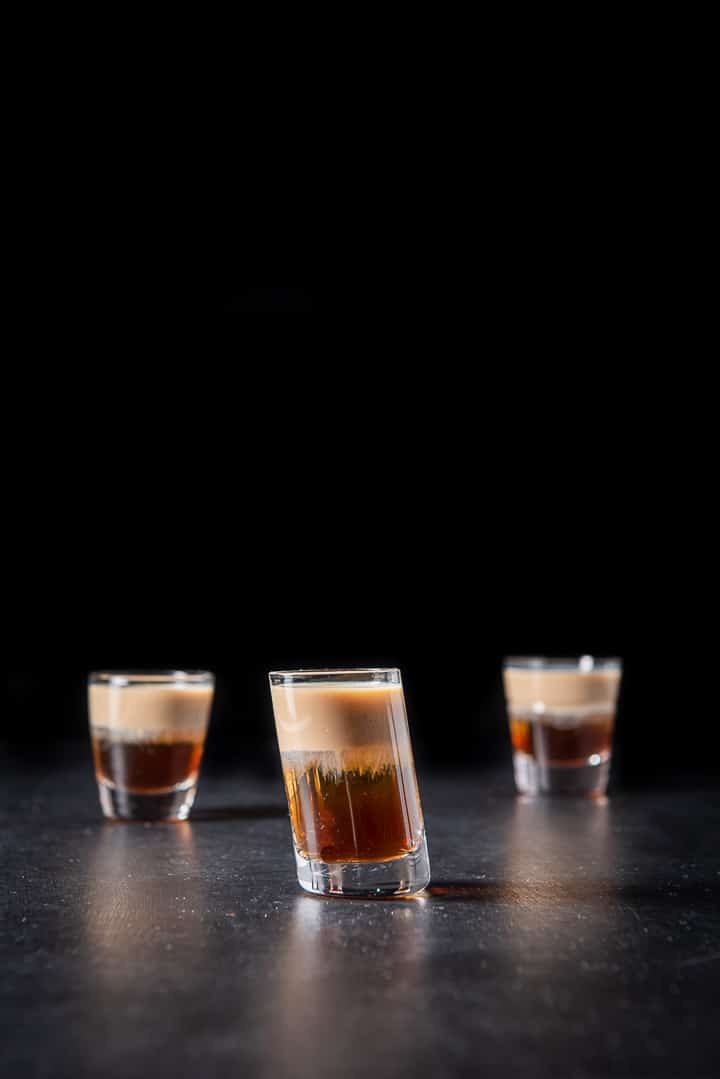 Tilted glass filled with the peanut butter and jelly shot