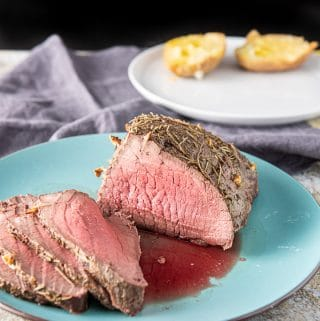 Slices of the roast beef dinner with a plate of potato in the background