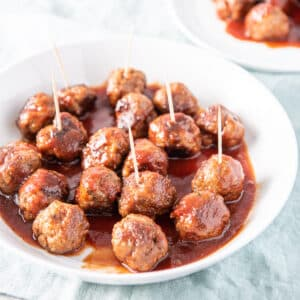A white plate with bourbon meatballs on it