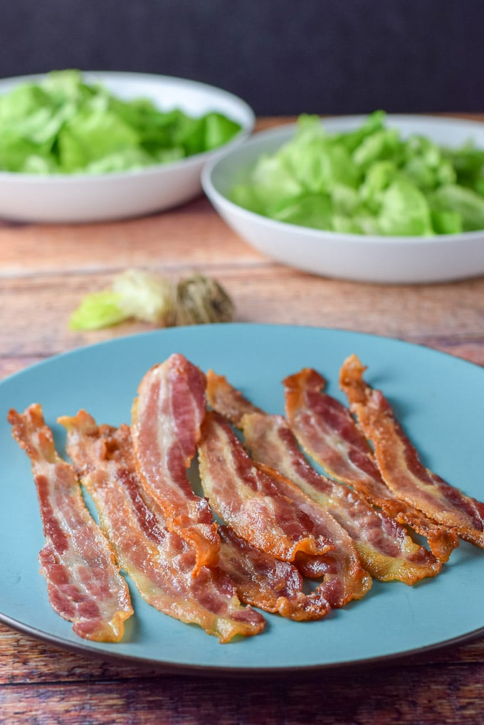 Bacon cooked with Boston lettuce in the background for the pear and pomegranate salad