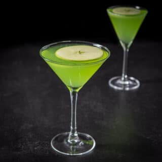 Sour appletini cocktail in the classic martini glass