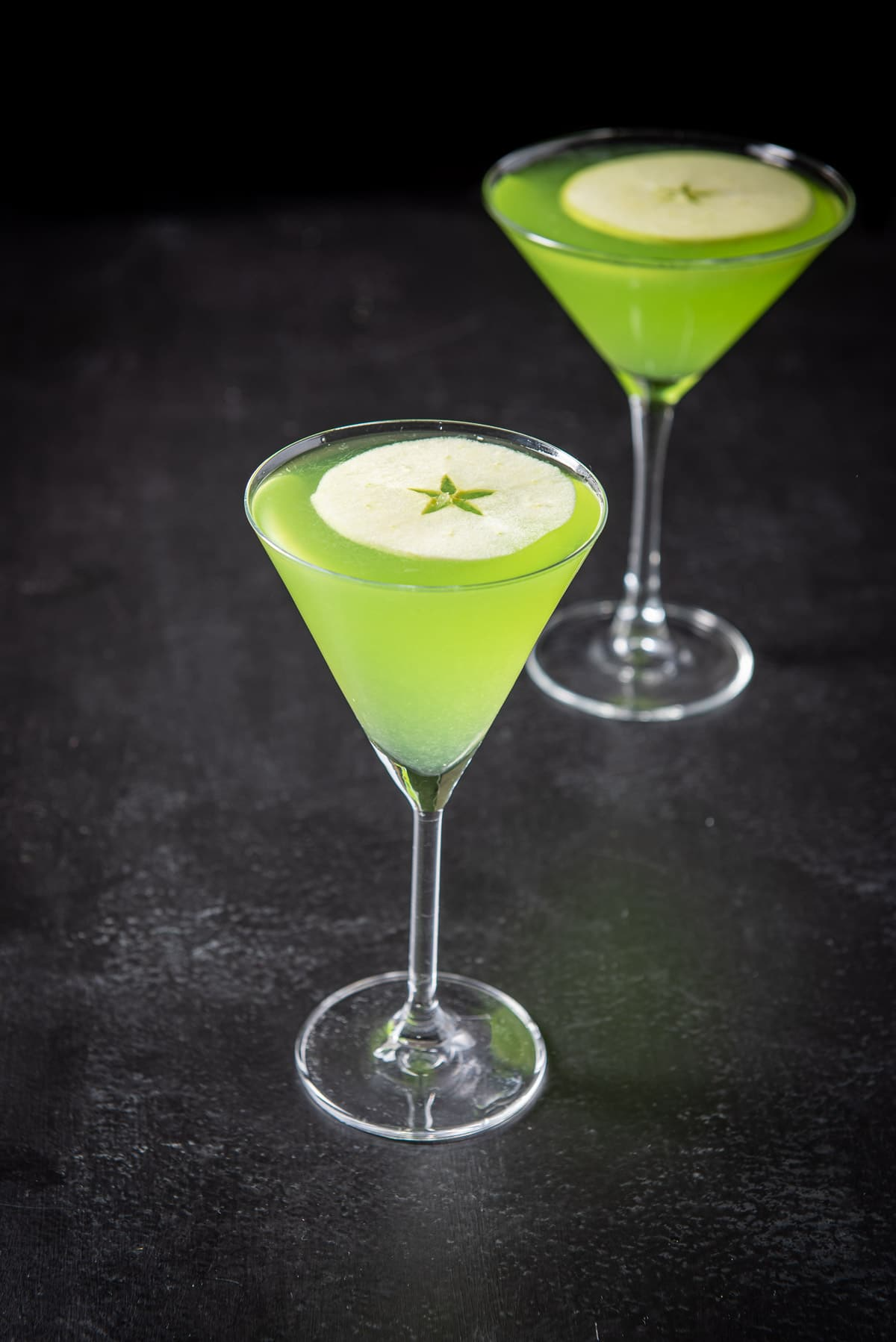 Thin martini glass filled with the sour appletini cocktail