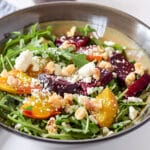 A brown bowl filled with salad with yellow and red beets, cheese and crumbled cheese - square