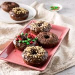 A pink plate of baked chocolate donuts - square