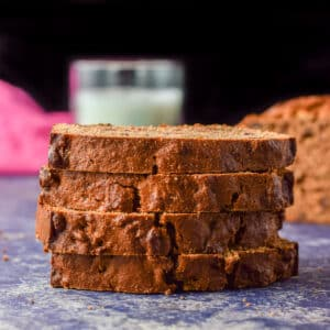 Four slices of date nut bread on top of each other with the loaf off to the left - square