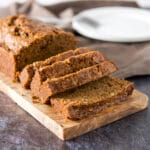 Slices of zucchini bread on a wooden board with a plate in the background - square