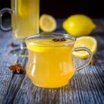 The short glass mug filled with a golden drink with star anise and a lemon wheel in it - square
